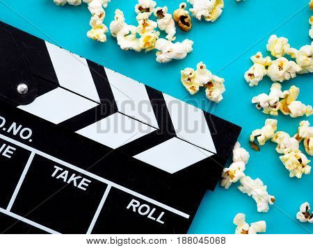 Popcorn and clapperboard on blue background. the concept of movie film entertainment advertising
