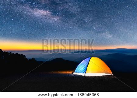 Landscape of Milky Way in night sky over mountain. Small Yellow Camping Tent Picnic Illuminated on top mountain Recreation and outdoor travel concept