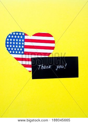 Thank you sign on a chalkboard with American flag on yellow background USA