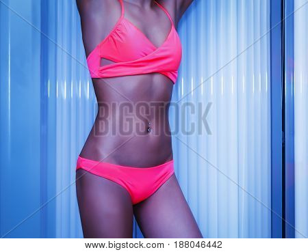 Slim Woman Standing In Solarium Getting Sun Tan