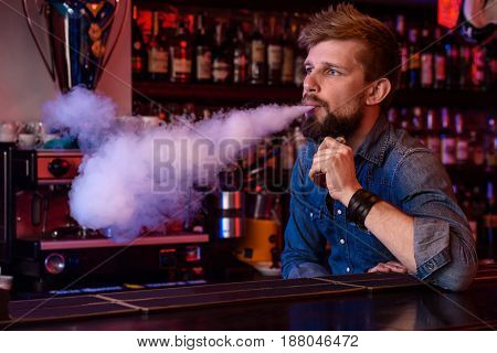 Vape. Vaping man in a cloud of vapor. Photo is taken in a vape bar. Vape shop