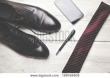 man shoes tie and phone on wooden table