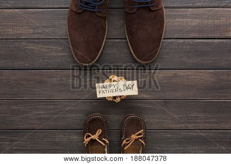 Happy Fathers Day background on rustic wood with male and child shoes