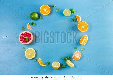 citrus food circle frame pattern on blue background - assorted citrus fruits with mint leaves