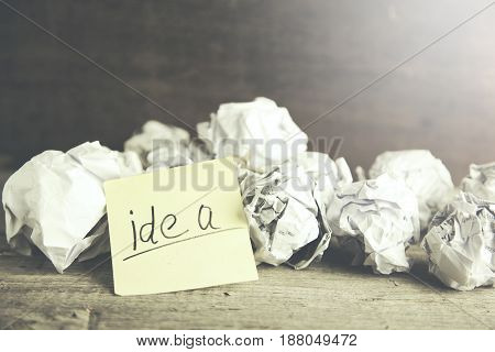 sheet of paper with word idea and crumpled on table.