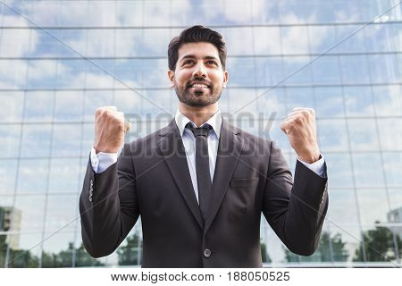 Successful happy smiling arabic eastern indian businessman or worker in black suit with tie and shirt with beard standing in front of an office building with raised hands on green grass in summer day.