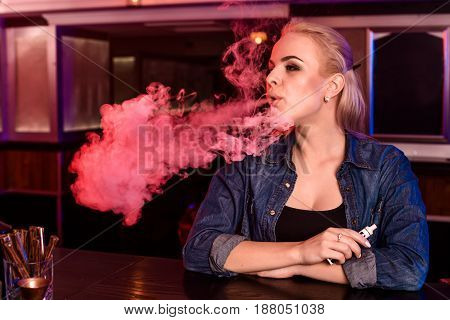 Young pretty woman smoke an electronic cigarette at the vape bar. Vape shop.