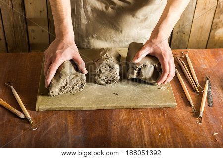 pottery, clay, ceramics art concept - closeup on hands of young master with the large pieces of fireclay, male dressed in apron, ceramist with raw materials on wooden table with sculpting tools set