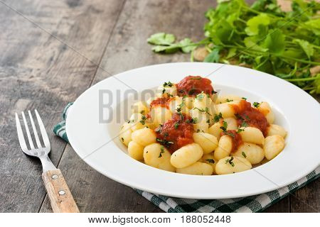 Gnocchi with tomato sauce on wooden background
