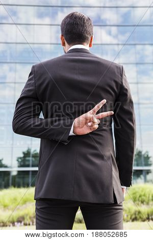Businessman or worker wothout face in black suit standing with his back to camera and shows peace sign or victory hand in front of an office building.