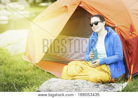 A girl sitting near a tent in a campsite on the river bank.