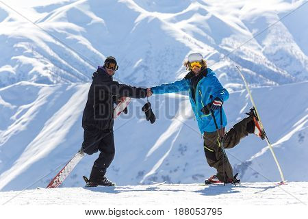 Two Skier Shake Hands During Descent At A Ski Resort. Beautiful Winter Landscape With Snow-topped Mo