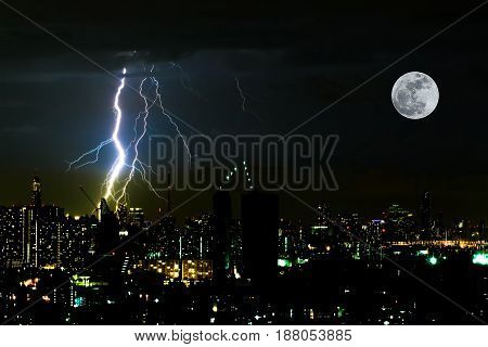Dramatic thunder storm lightning bolt on the horizontal sky and city scape with super moon