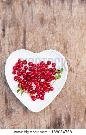 Fresh red forest cranberries in heart plate on wooden background autumn design