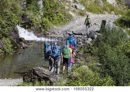 HIMALAYAS ANNAPURNA REGION NEPAL - OCTOBER 13 2016 : Hikers with backpack on trekking trail in Himalayas mountains. Four of tourists are on a path to Annapurna - Nepal Himalayas