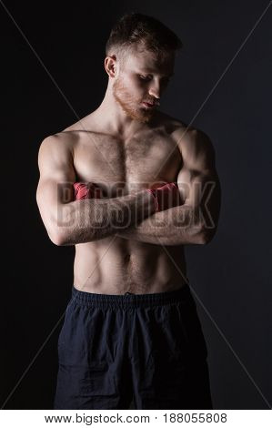 Bearded man with boxing bandages on black background