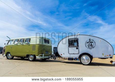 Scheveningen beach the Netherlands - May 21 2017: Green VW kombi camper wagen and teardrop trailer at Aircooled classic car show