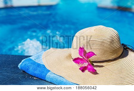Straw hat with orchid flower and blue towel near swimming pool - holiday tropical concept