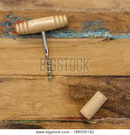 Old-fashioned corkscrew with cork, shot from above on distressed wooden background texture with plenty of copy space. Square design template for wine list or a tasting invitation, slightly toned