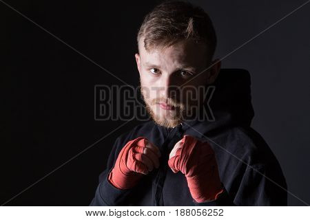 Fighter man wearing tracksuit on black background