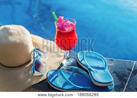 Watermelon fresh juice smoothie drink glass with flower, sunglasses, slippers and straw hat on border of a swimming pool - holiday tropical concept