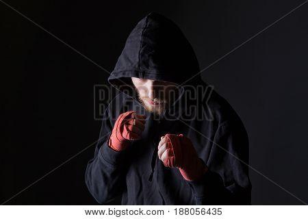 Fighter bearded man wearing hood on black background
