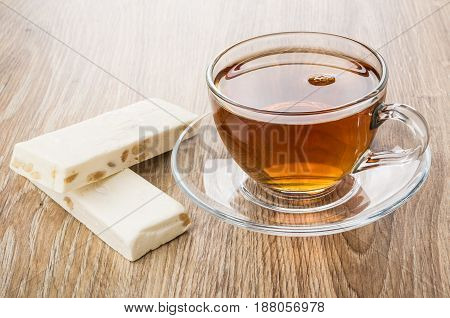 Two pieces of nougat with nuts and transparent cup with tea on wooden table