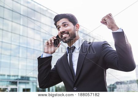 Successful happy smiling arabic eastern indian businessman or worker in black suit with beard calling with his phone near his ear standing in front of an office building with raised hand celebrating.