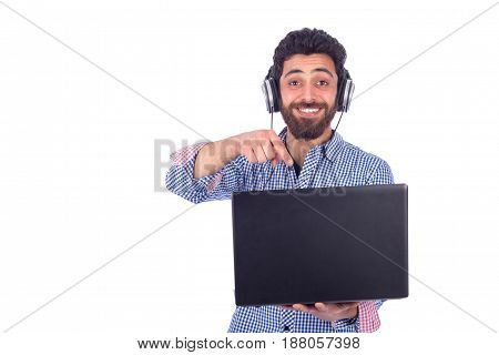 smiling beard yung man listening to music and pointing to black labtop guy wearing blue shirt isolated on white background