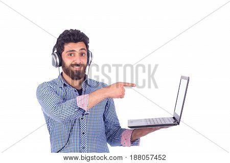 smiling beard yung man listening to music and pointing to labtop guy wearing blue shirt isolated on white background