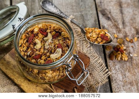Granola in glass jar on rustic wood background
