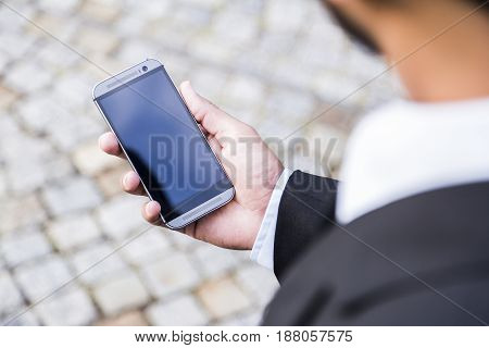 Man with beard in black suit and white shirt holds modern mobile phone with touch screen in his hand on background of pavement road