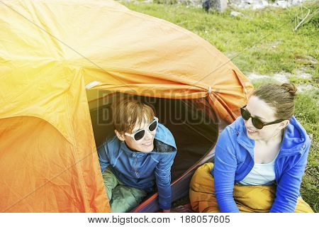 The girls are sitting near a tent in a campsite on the river bank.