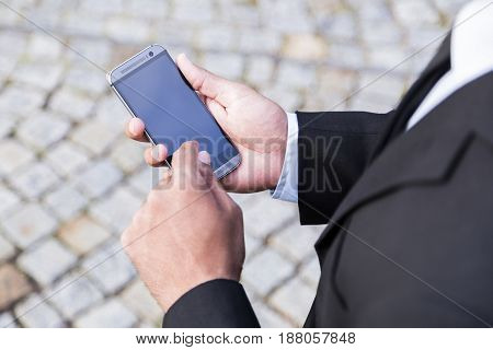 Man in black suit and white shirt holds modern mobile phone with touch screen in his hand and clicks on the screen on background of pavement road.