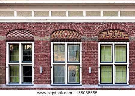 Front Beautiful Old Flat House Facade Pattern From Red Brick With White Window Frame. Vintage Buildi