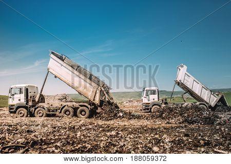 Industrial Heavy Duty Dumper Trucks Unloading At Construction Site