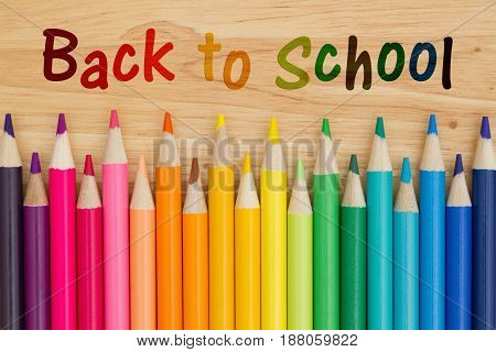 Back to School text with colorful pencil crayons on a desk