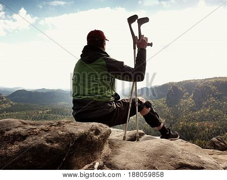 Tired Tourist With Medicine Crutch  And Broken Leg Fixed In Immobilizer Resting On Summit.
