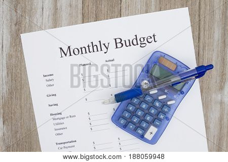 Creating a monthly budget A print out of a monthly budget with pen and calculator on weather wood