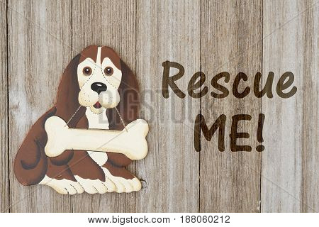 Rescuing a dog A wood dog with a bone on a weathered wood background with text Rescue me