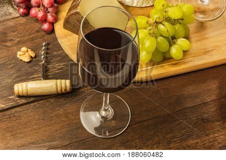 A glass of red wine at a tasting, with a piece of cheese and grapes in the background, a corkscrew, and a place for text, on a dark rustic texture