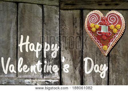 Illustration made with photo of old wooden fence in the background, photo of heart-shaped cookie on the upper layer and added text