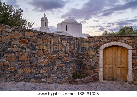 A small white church behind a stone wall. Evening time. The coast of Mirabello Bay. Elounda. Crete. Greece