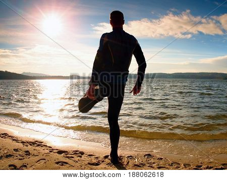 Silhouette Of Person In Sportswear And Short Hair  On Beach See Into Sun Above Sea