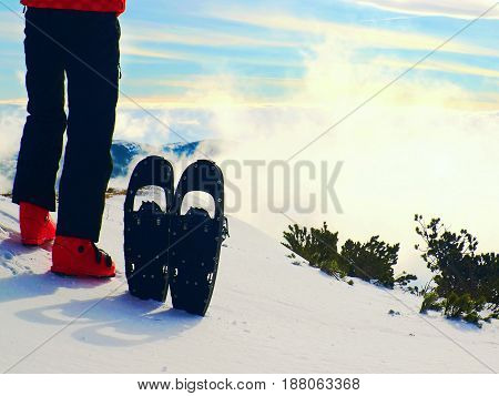 Skier In Red Winter Jacket With  Fun Snowshoes Stay In Snow In Mountains.