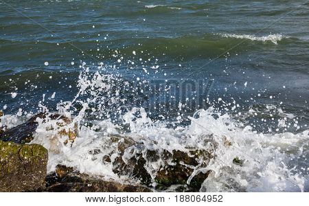 Waves breaking onto a stony seashore. Close-up.