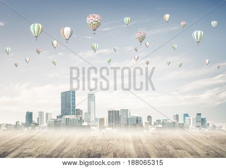 Modern cityscape with buildings and skyscrapers covered with fog and balloons in sky