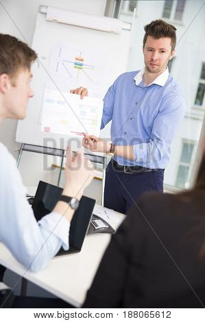 Confident male professional showing chart to colleagues in office