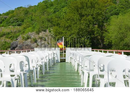 desolate deck of a walking, river ship with a German flag at the stern