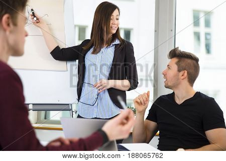 Young businesswoman explaining graph to male colleagues in office